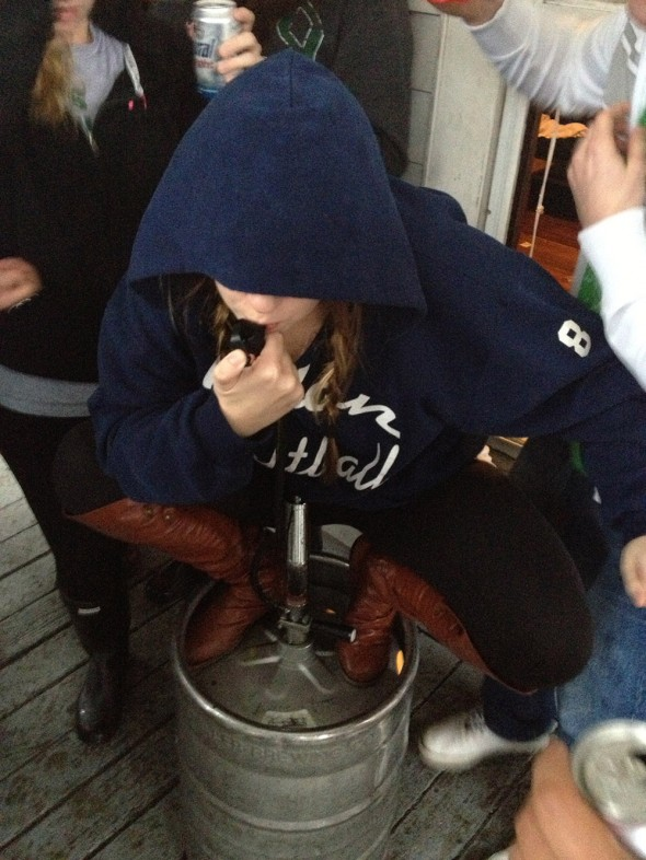 Chugging beer and wearing a blue hoodie, just like the fugitive's description.
